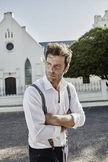 Portrait of man in old-fashioned clothes at a church in the countryside - RORF02034