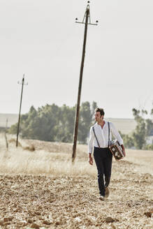 Man in old-fashioned clothes walking with suitcase in the countryside - RORF02046