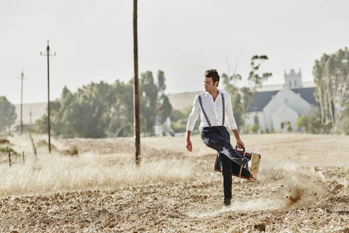 Man in old-fashioned clothes with suitcase in the countryside - RORF02049