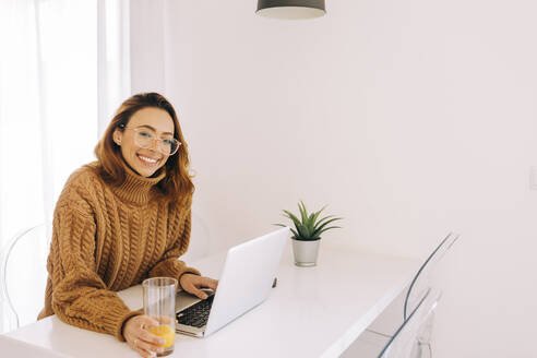 Portrait of smiling young woman using laptop at home - DCRF00148