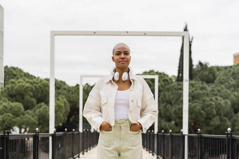 Portrait of a confident woman with headphones on a bridge - AFVF05732