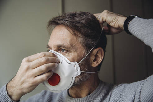 Mature man putting on protective mask - MFF05078