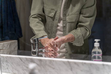 Mirror reflection of man, washing hands with sanitizer - AFVF05762