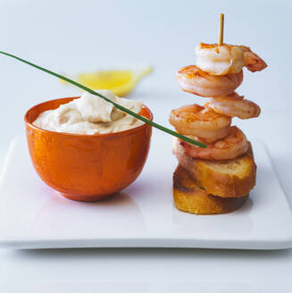 Bowl ofaiolisauce and skewered shrimps - PPXF00296