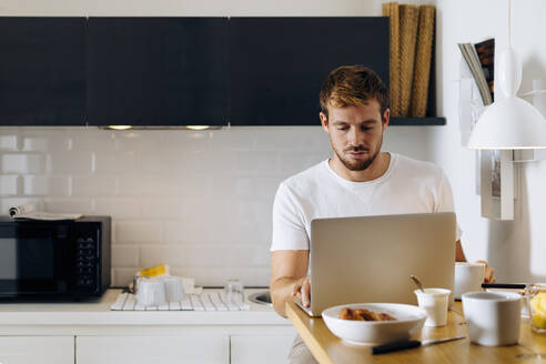 Young man using laptop in kitchen - SODF00700