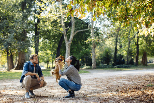 Happy young couple with dog in a park - SODF00712