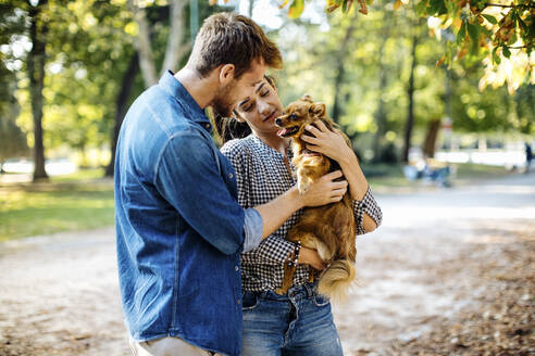 Happy young couple with dog in a park - SODF00718