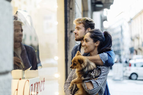 Young couple with dog looking in shop window in the city - SODF00733