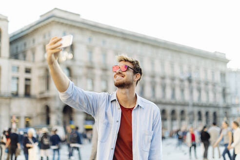 Smiling young man taking a selfie in the city, Milan, Italy - SODF00736