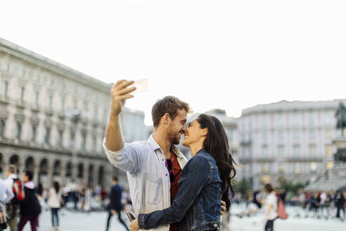 Happy young couple taking a selfie in the city, Milan, Italy - SODF00742