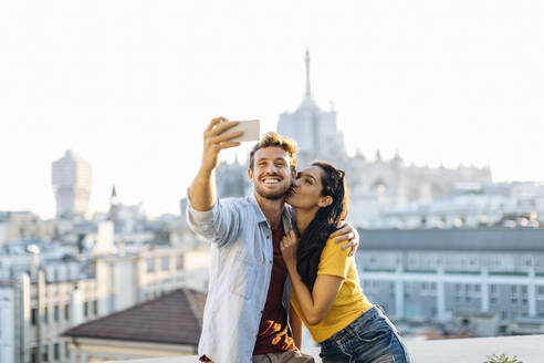 Happy young couple taking a selfie above the city, Milan, Italy - SODF00745