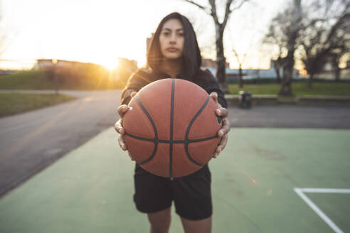 Young sportive woman posing holding basketball on court at sunset - MEUF00099