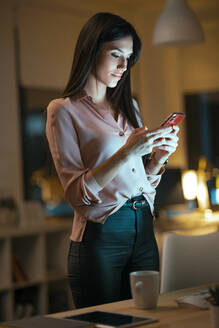 Portrait of young woman using smartphone in office - JSRF00924