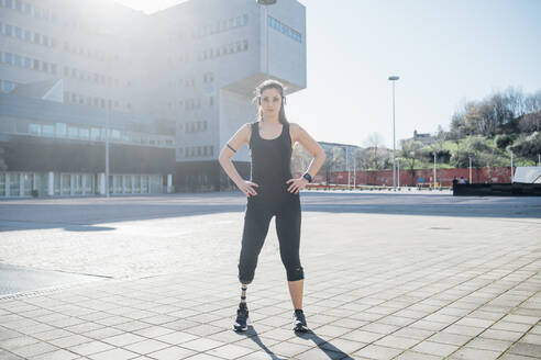 Portrait of confident sporty young woman with leg prosthesis in the city - MEUF00125