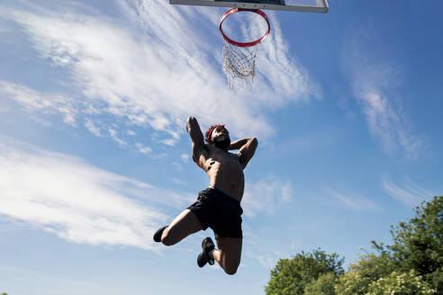 Man playing basketball, dunking - JPIF00503