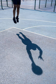 Shadow of a man playing basketball on basketball court, dunking - JPIF00506