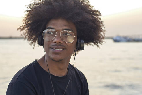 Portrait of young man wearing glasses and listening to music - VEGF01778