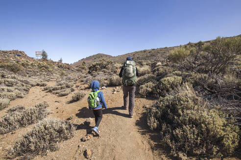 A father and his son trekking in the Arenas Negras area, Teide National Park, Tenerife, Spain - IHF00287
