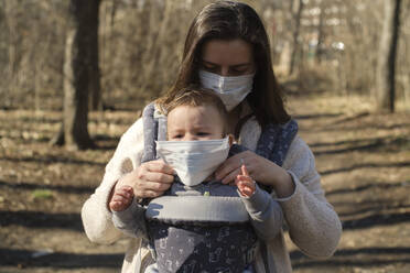 Mother protecting her baby from seasonal virus - BZF00534