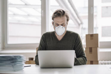 Businessman wearing protective mask and using laptop - JOSEF00112