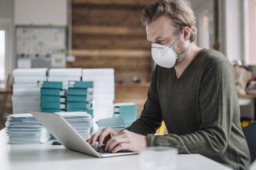 Businessman wearing protective mask and using laptop - JOSEF00115