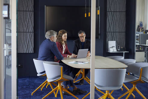 Two businessmen and businesswoman working together on a project in office - RBF07139