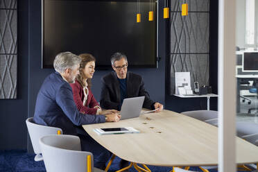 Two businessmen and businesswoman working together on a project in office - RBF07142