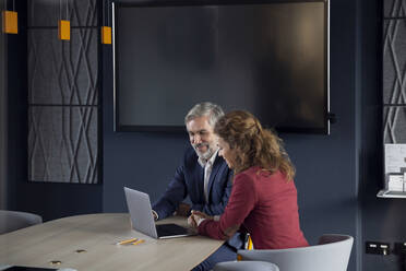 Businessman and businesswoman working together on a project in office - RBF07145