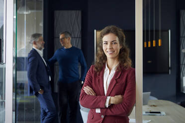 Portrait of confident businesswoman in office with colleagues in background - RBF07151