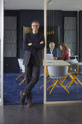 Portrait of confident businessman in office with colleagues in background - RBF07154