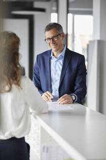 Smiling businessman looking at businesswoman in office - RBF07163