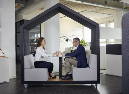 Smiling businessman and businesswoman sitting in a wheeled cubicle in office - RBF07169