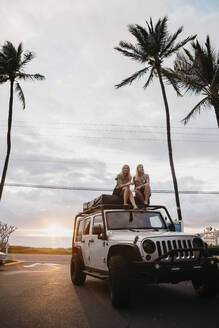 Full length of female friends sitting on jeep against palm trees and cloudy sky, USA, Hawaii, Maui - LHPF01200