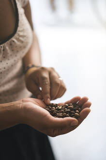 Close-up of woman with coffee beans in her hand - JPIF00516