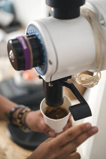 Close-up of woman pouring coffee into cup from a machine - JPIF00537