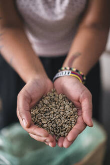 Close-up of woman with coffee beans in her hands - JPIF00549