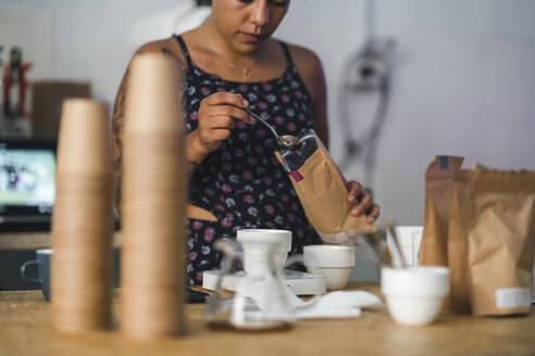 Woman working in a coffee roastery preparing coffee - JPIF00555