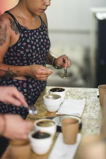 Woman working in a coffee roastery preparing coffee - JPIF00558