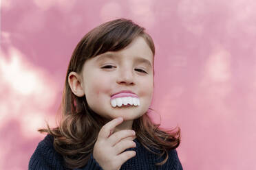 Portrait of little girl with false candy teeth in front of  pink background - GEMF03490
