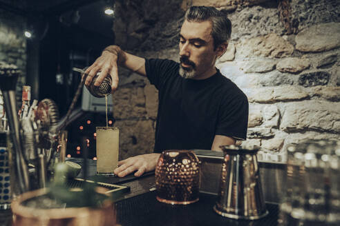 Bartender pouring cocktail in a glass - MTBF00362