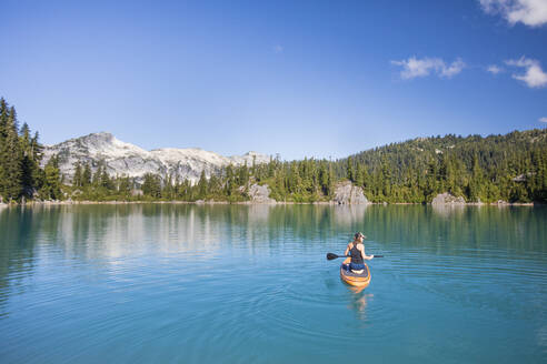 Active woman paddles Stand up paddle board on blue lake. - CAVF77434