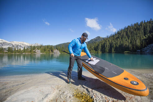 Adventurous man prepares to use SUP on remote alpine lake. - CAVF77437