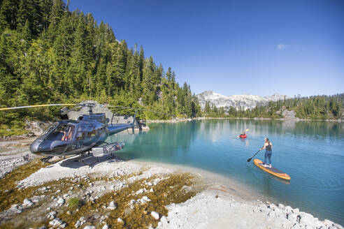 Mother and daughter paddling on stunning blue lake during tour. - CAVF77446
