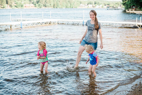 A mother and her girls cooling off at the lake. - CAVF77530