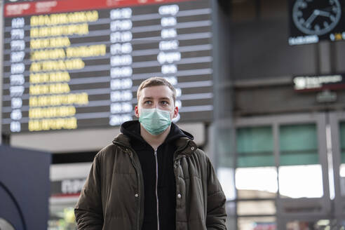 Young man with face mask at train station in the city - VPIF02126