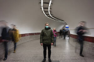 Young man with face mask standing isolated in subway underpass, with people moving around him - VPIF02129