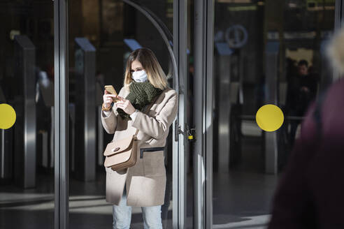 Woman with face mask, using smartphone at subway station - VPIF02135
