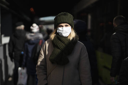 Woman with face mask standing at bus stop - VPIF02138
