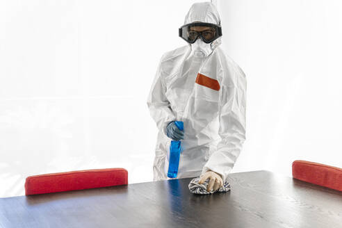 Woman wearing protective clothes, sanitizing her home, wiping table - DLTSF00631