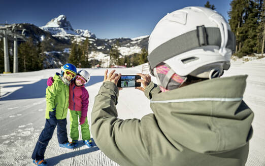 Mother photographing her children on ski slope - DIKF00389